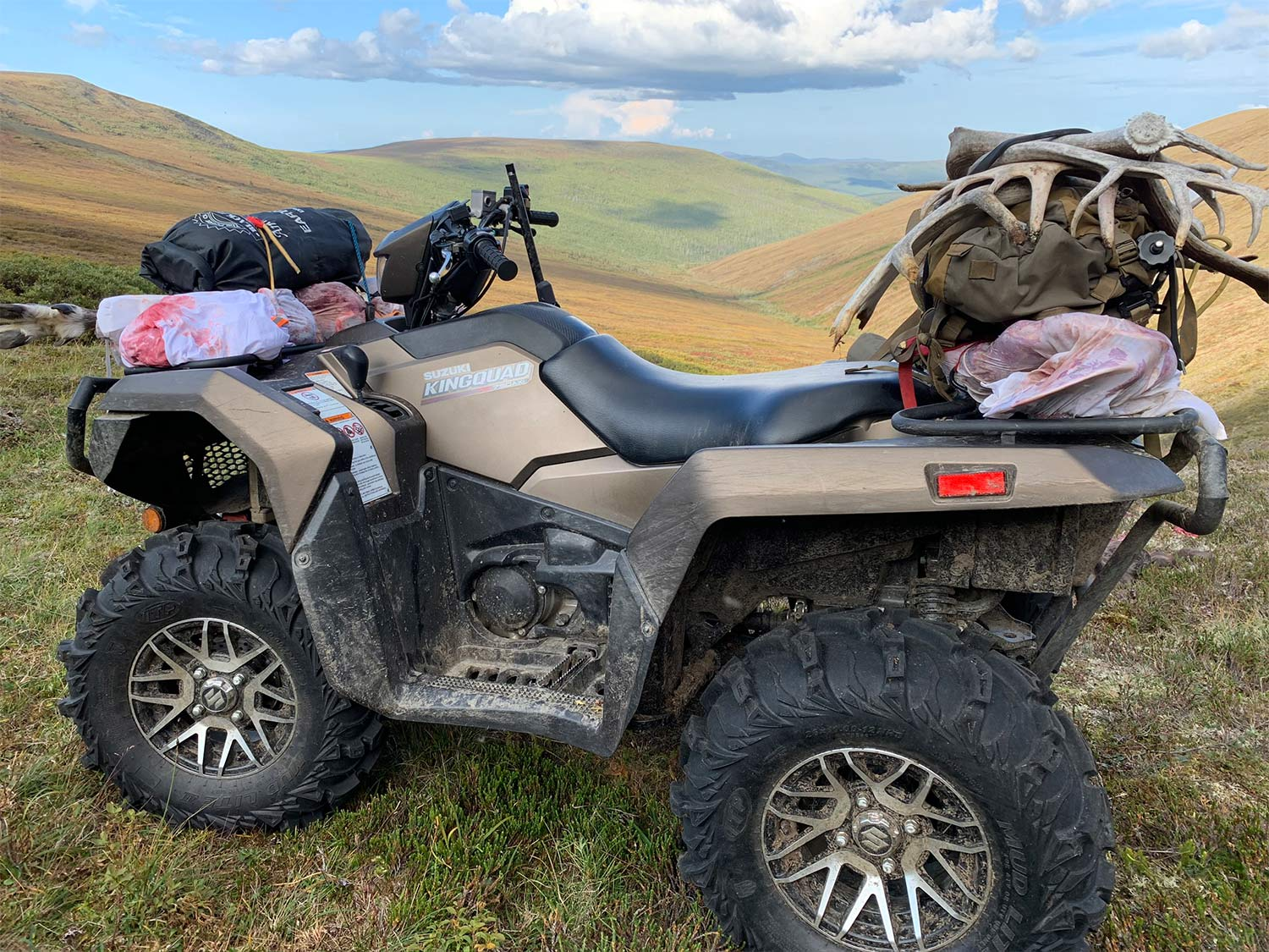 A four-wheeled ATV loaded with hunting gear sits atop a hill with a sprawling view of hills and plains in the background.