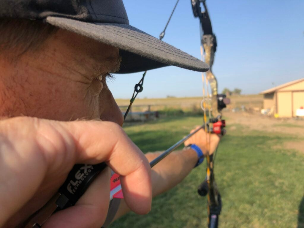 A bowhunter practicing in the yard holds the Diamond Edge 320 bow at full draw.