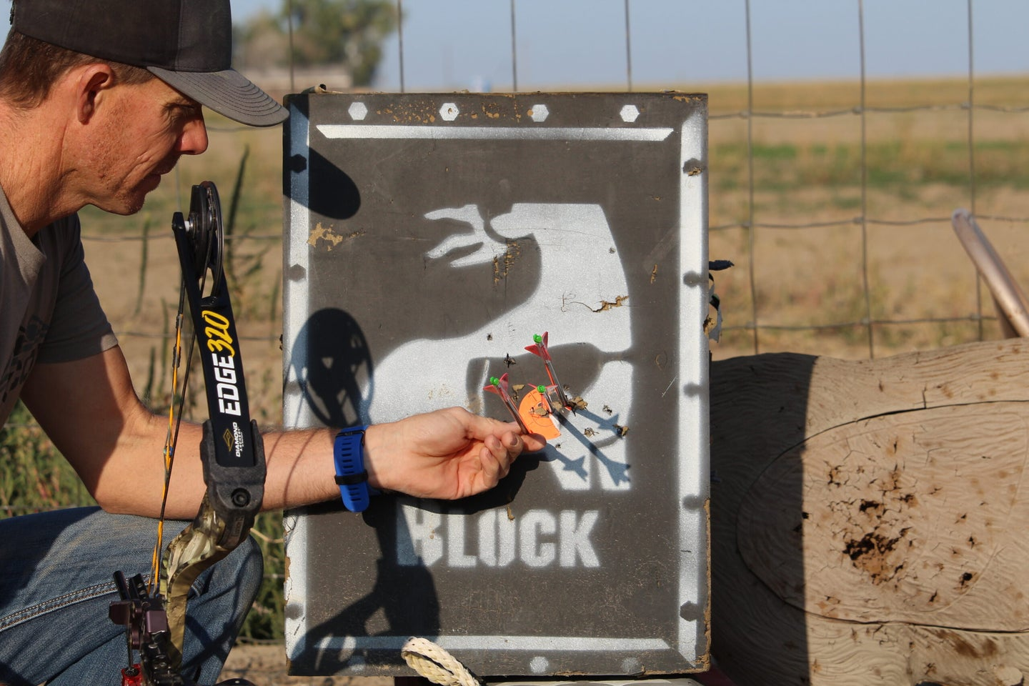 An archer examines arrow groups in a block target while holding a Diamond Edge 320 bow.