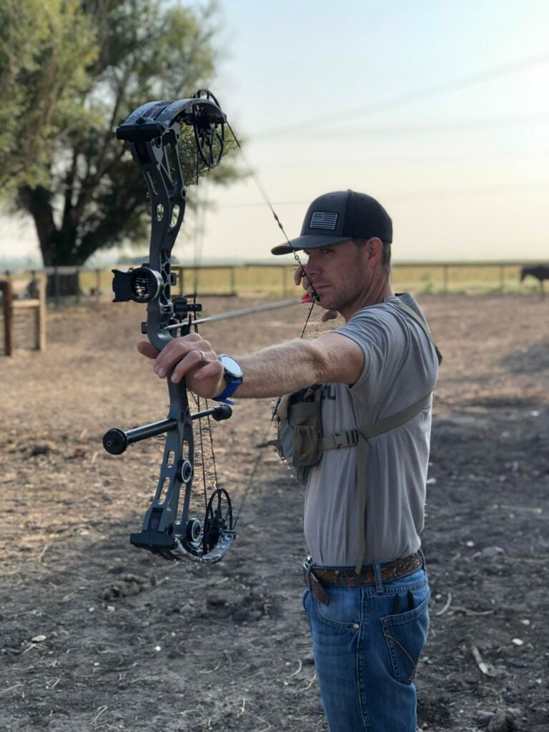 A bowhunter practices in the yard with his Bowtech Revolt at full draw.