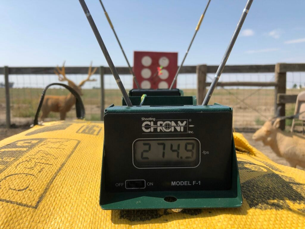 A chronograph resting on a yellow bag target on the archery range displays 274.9 feet per second.