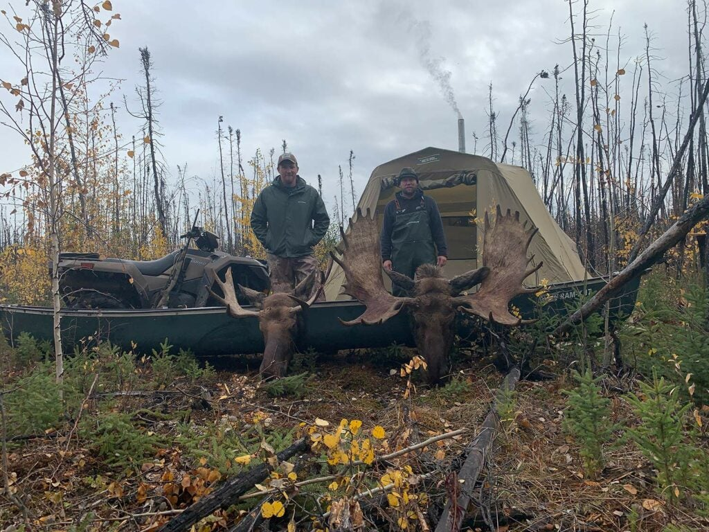 Two hunters stand at a campsite next to a canoe and a four-wheeled ATV. There are two moose heads nearby.