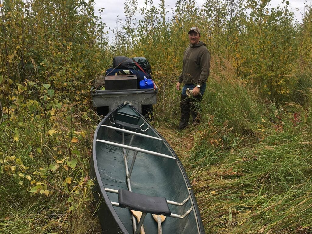 A four-wheeled ATV drags a canoe behind it on an overgrown hunting trail.