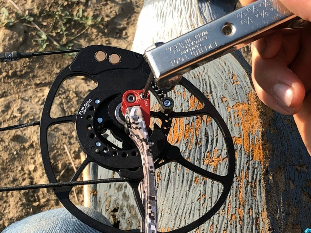 A hand uses a hex wrench to adjust the DeadLock cam on a Bowtech Revolt compound hunting bow.
