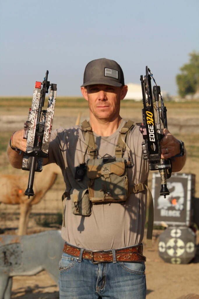 A bowhunter holds a compound bow in each hand while standing on his home archery range.