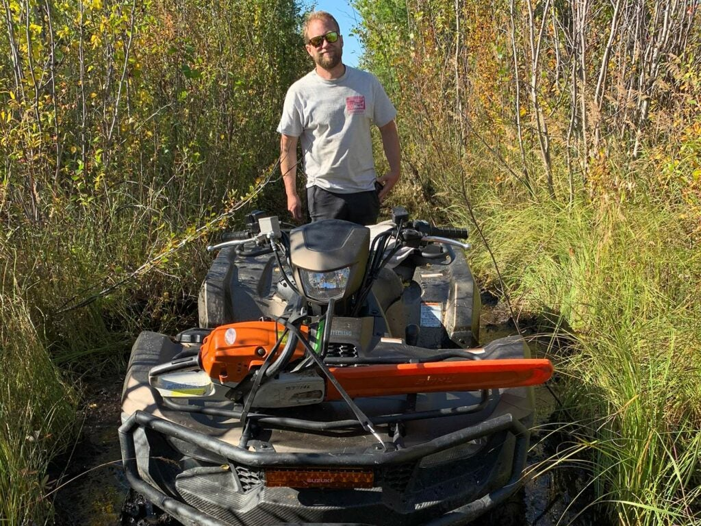 A man stands behind a four-wheeled ATV in very dense brush and woods, on a hunting trail.