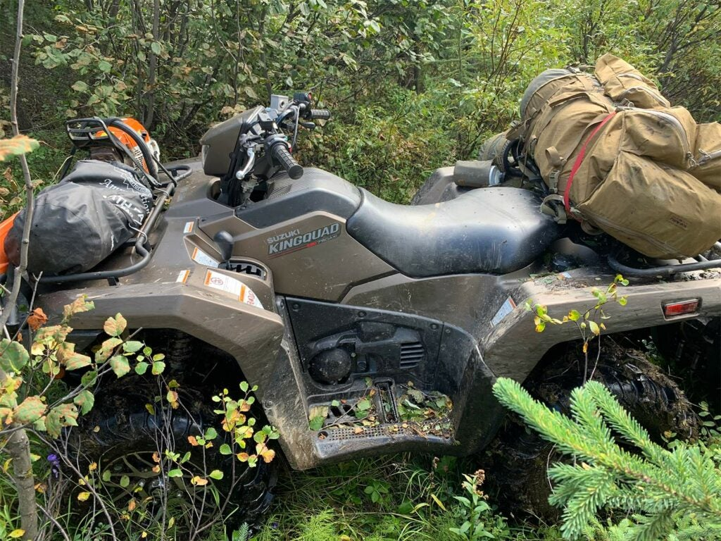 A four-wheeled ATV laden with hunting gear is surrounded by thick brush and bushes.