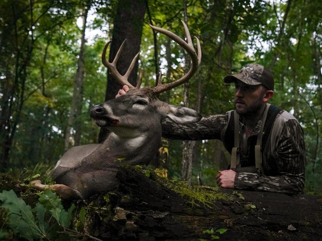 A man in full camo holds up the head of a whitetail buck by the antlers. They are in a lush, overgrown wooded area surrounded by trees, bushes, and other flora.