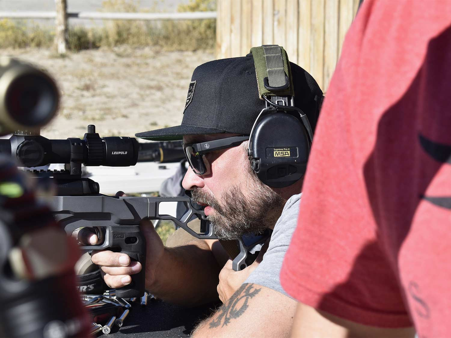 A man in glasses and hat looks through a rifle scope.