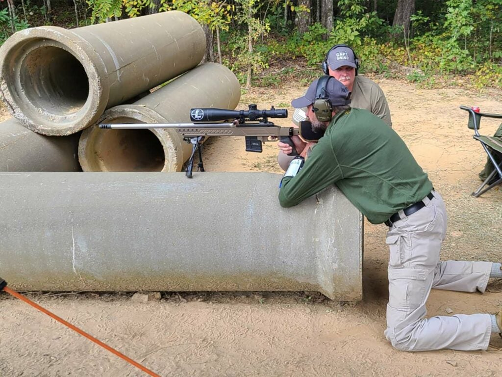 A man leans over a pipe and aims a rifle while glancing through a riflescope.