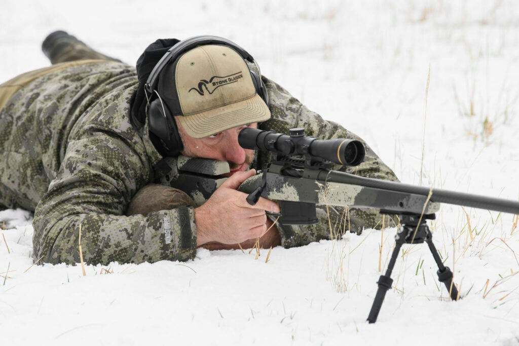A hunter in camo and a green hat lies prone on the ground behind a Springfield Waypoint rifle, in conjunction with a bipod.