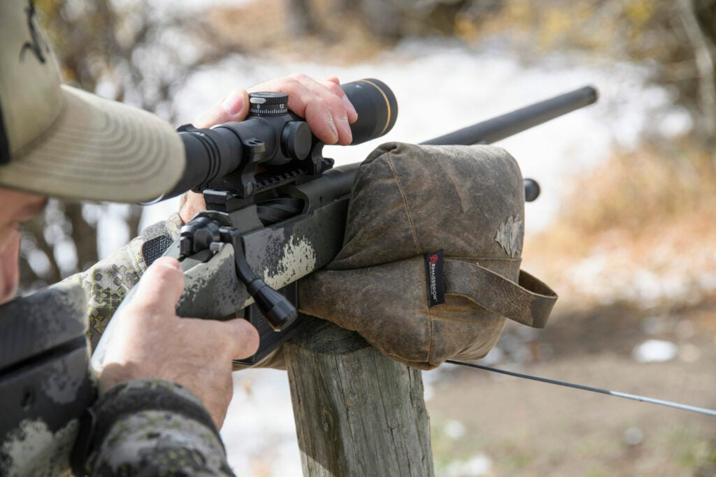 A hunter rests his Springfield rifle on a fence post using a shooting bag.