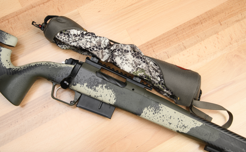 A scope cover in Badlands camo cinched over the scope on the Springfield Waypoint camo-stocked bolt-action hunting rifle.