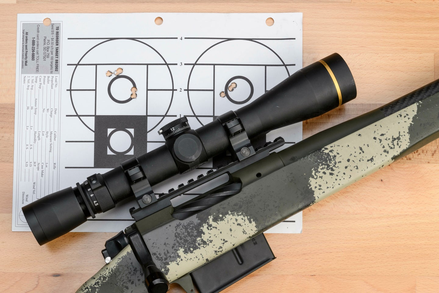 A camo-stocked bolt-action rifle, topped with a black scope, lying on top of a paper target with two zeroing groups.