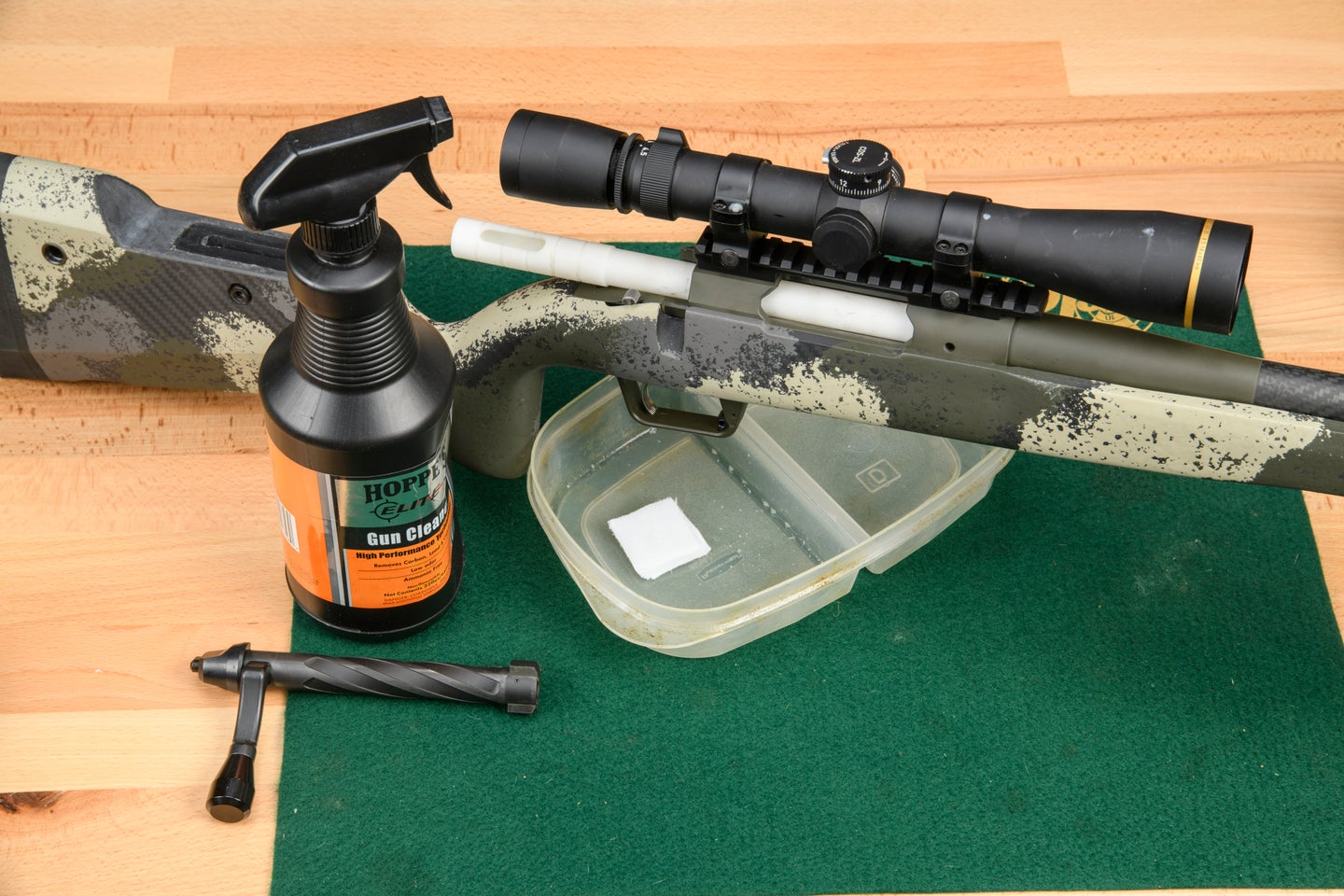 A rifle with a plastic cleaning tube in the bore, the bolt removed, a spray bottle of solvent, and a tupperware on a green felt pad.