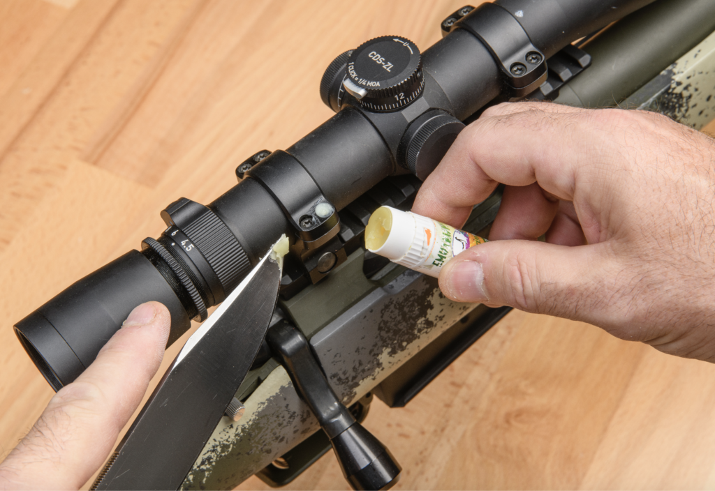 A pair of hands holds a chapstick tube and a knife-tip coated in chapstick while applying it to one of the screw heads on the riflescope bases.