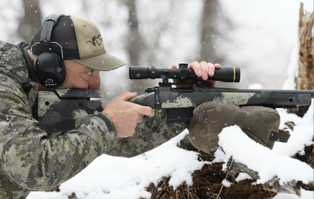 A hunter shoulders a rifle resting on a branch in the snowy woods. One hand is on the trigger, one is on the scope.