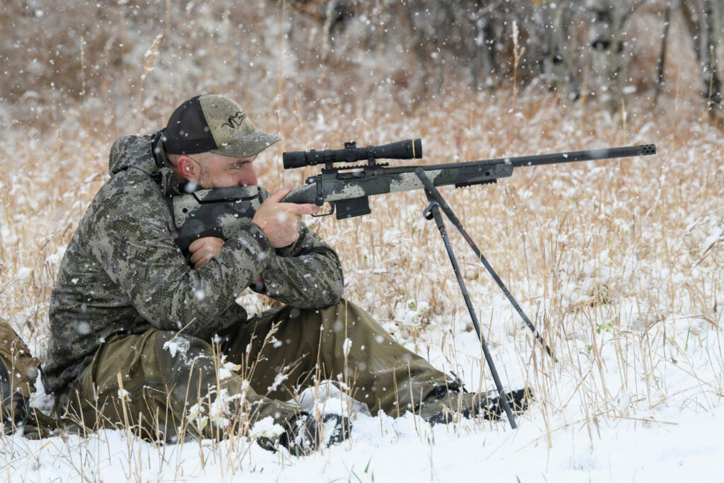Hunter sits behind a Springfield Waypoint rifle with a pair of shooting sticks in the snowy brush.