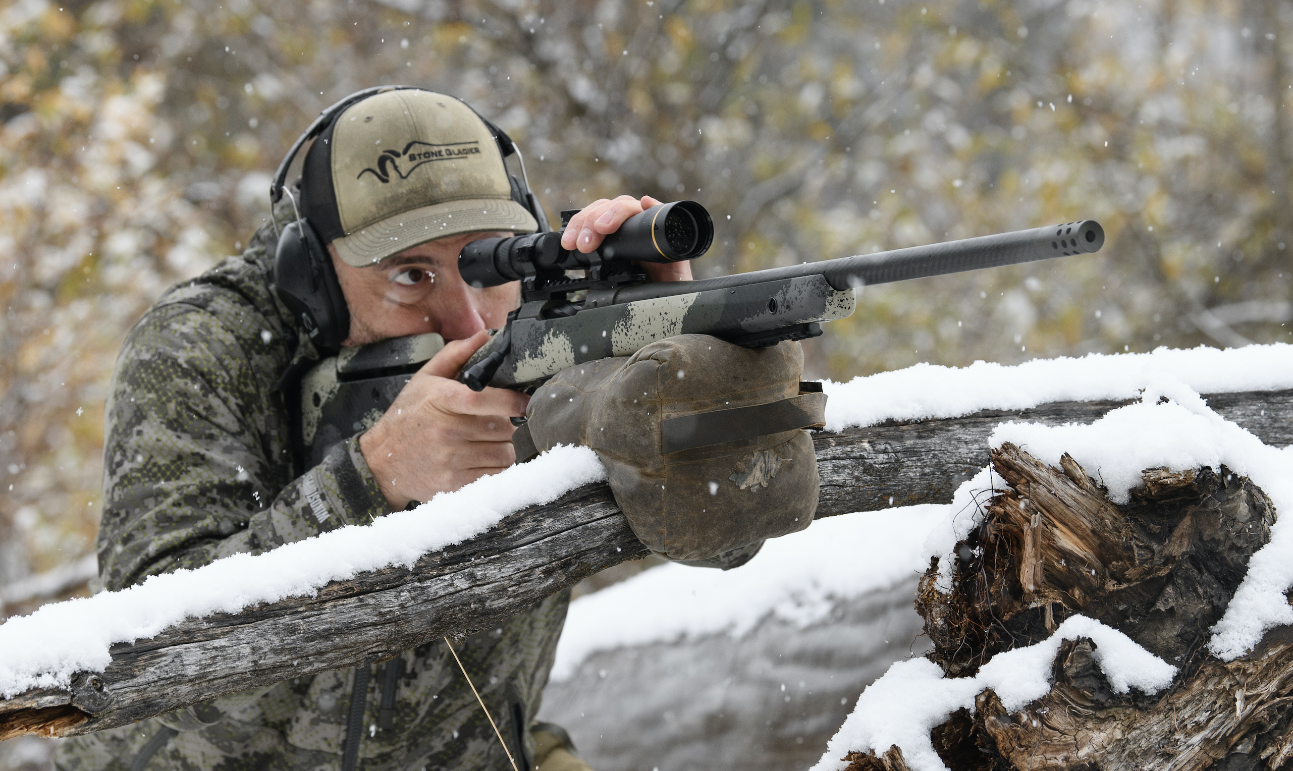 A hunter looks through the scope on his deer rifle, resting on a branch, in the snowy woods.