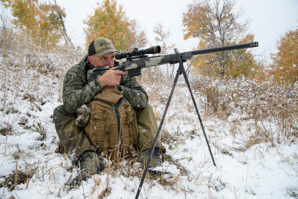 A hunter shoots his rifle off sticks on a snowy hillside while using a pack to steady himself.