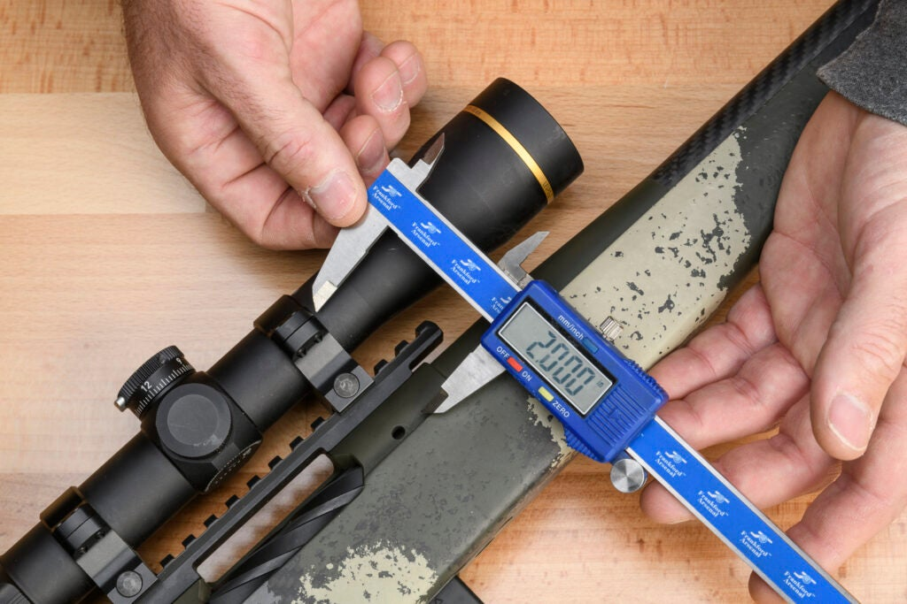 A pair of hands uses a blue digital caliper to measure the center of the rifle bore to the center of the scope.