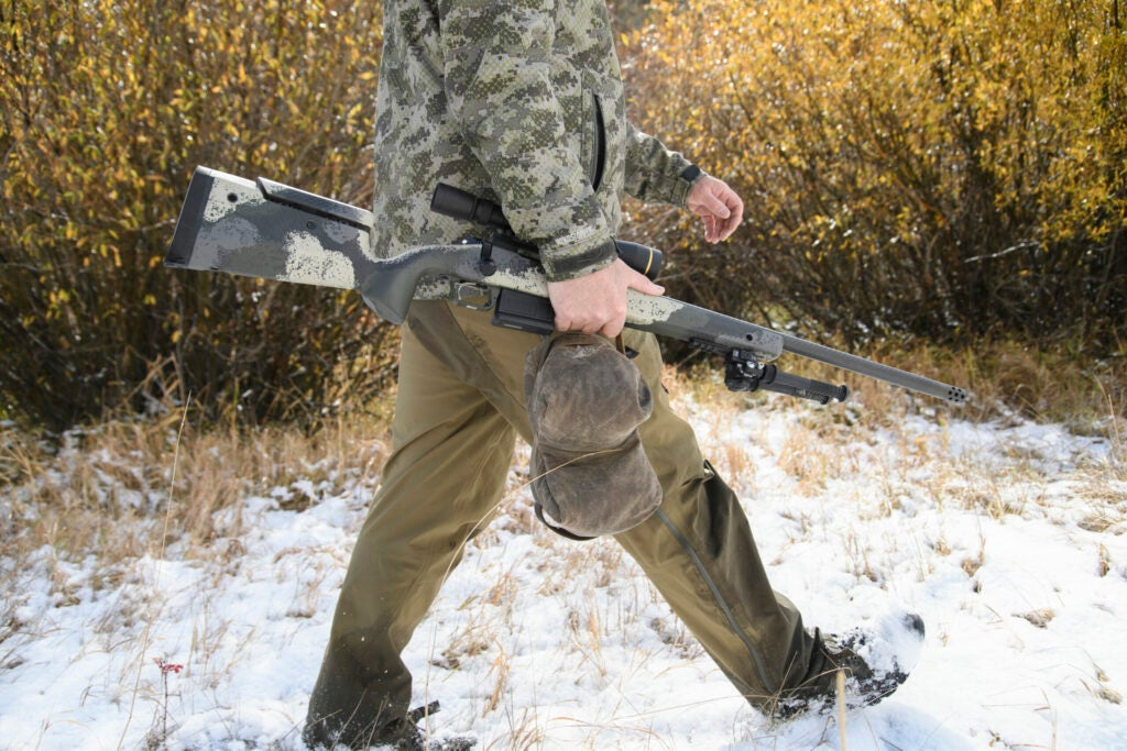 A hunter walks through the snow carrying a Springfield Waypoint rifle and a lightweight leather shooting bag.