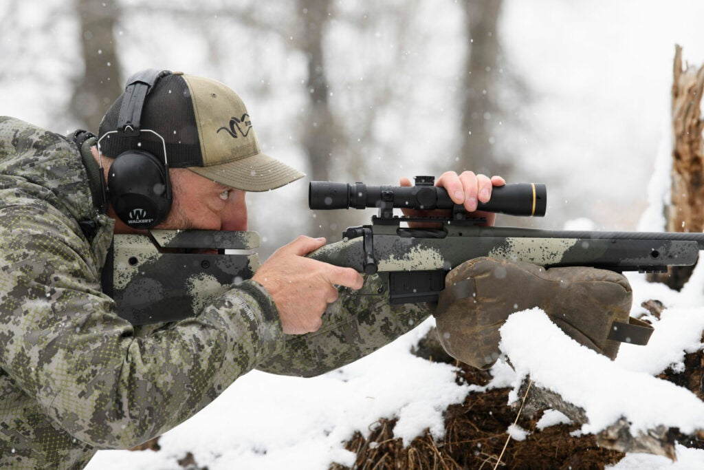 A hunter steadies his Springfield Waypoint bolt-action rifle on top of a shooting bag resting on a branch in a snowy field.