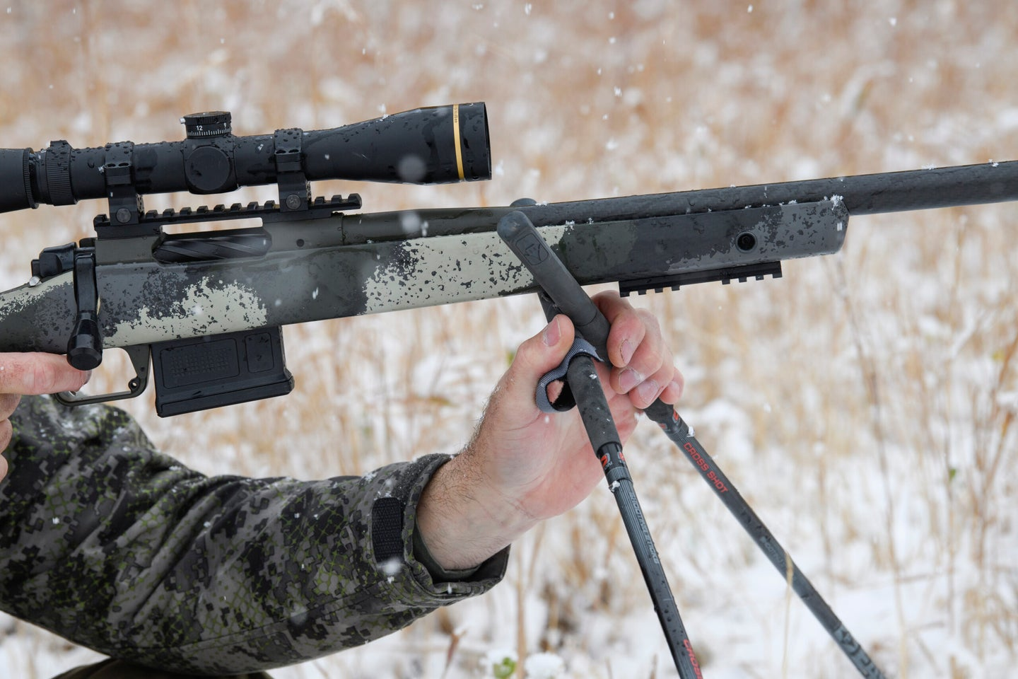 A hunter's hand adjusting the position and height of a pair of shooting sticks on the stock of a scoped Springfield rifle.