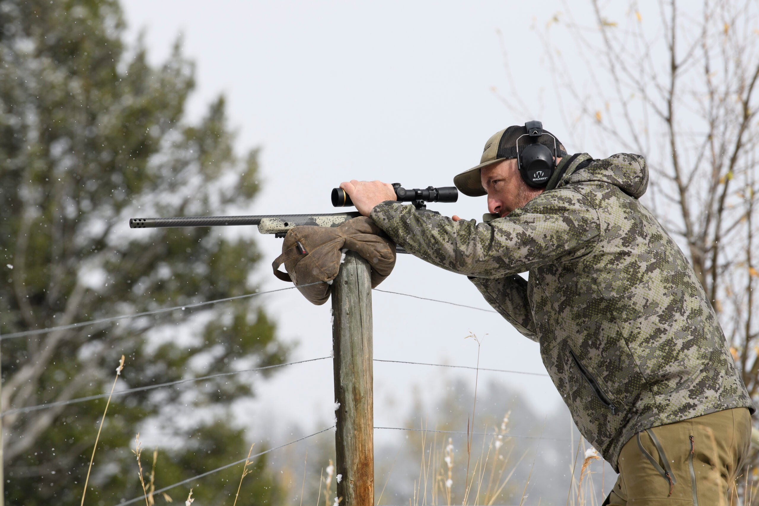 A Western hunter readies himself for a shot behind his bolt-action rifle, which is resting on a fence post.