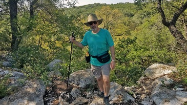 A man hikes through the woods wearing a fanny pack.
