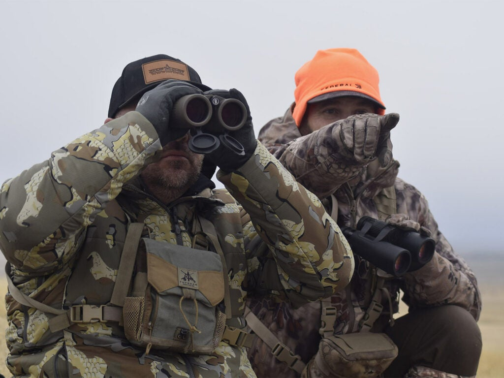 Two hunters scout a plain. One uses binoculars while the other points in a direction to scout.
