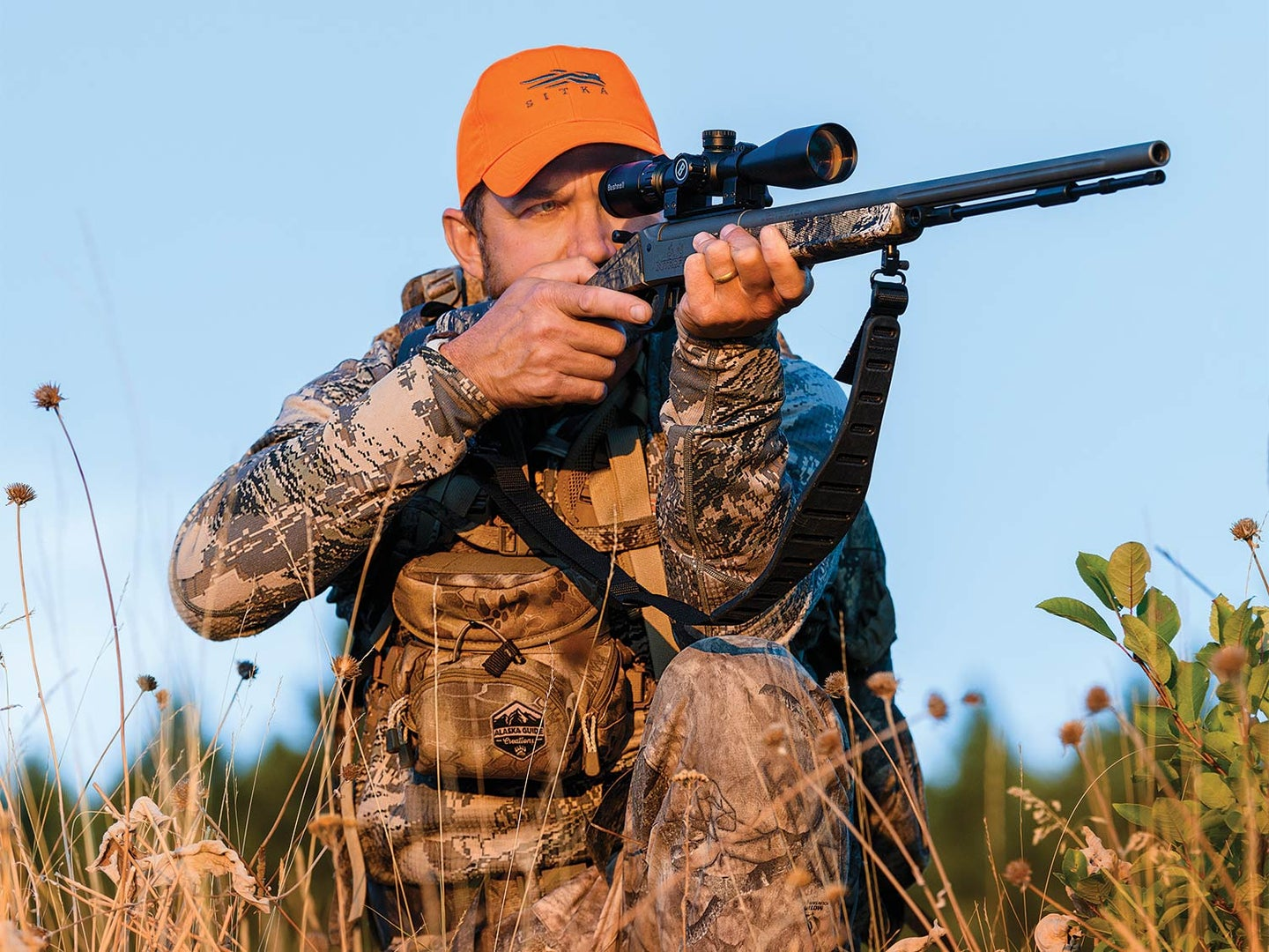 A hunter in full camo and orange cap holds a rifle to their shoulder while aiming, preparing to fire.