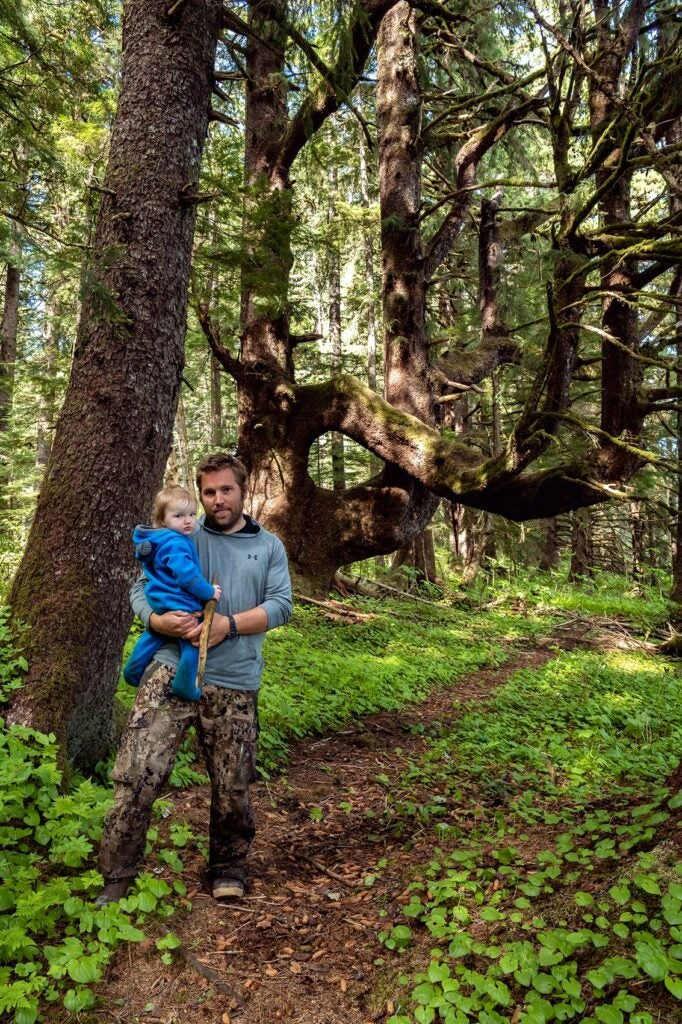 A man in a blue shirt and camo pants holds his young son in an old-growth forest.