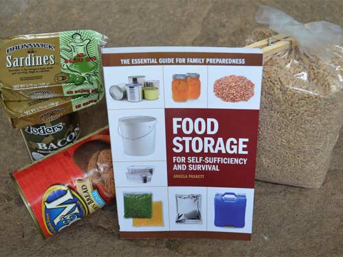 An assortment of supplies: Sardines, Beans, grains and a food storage book.