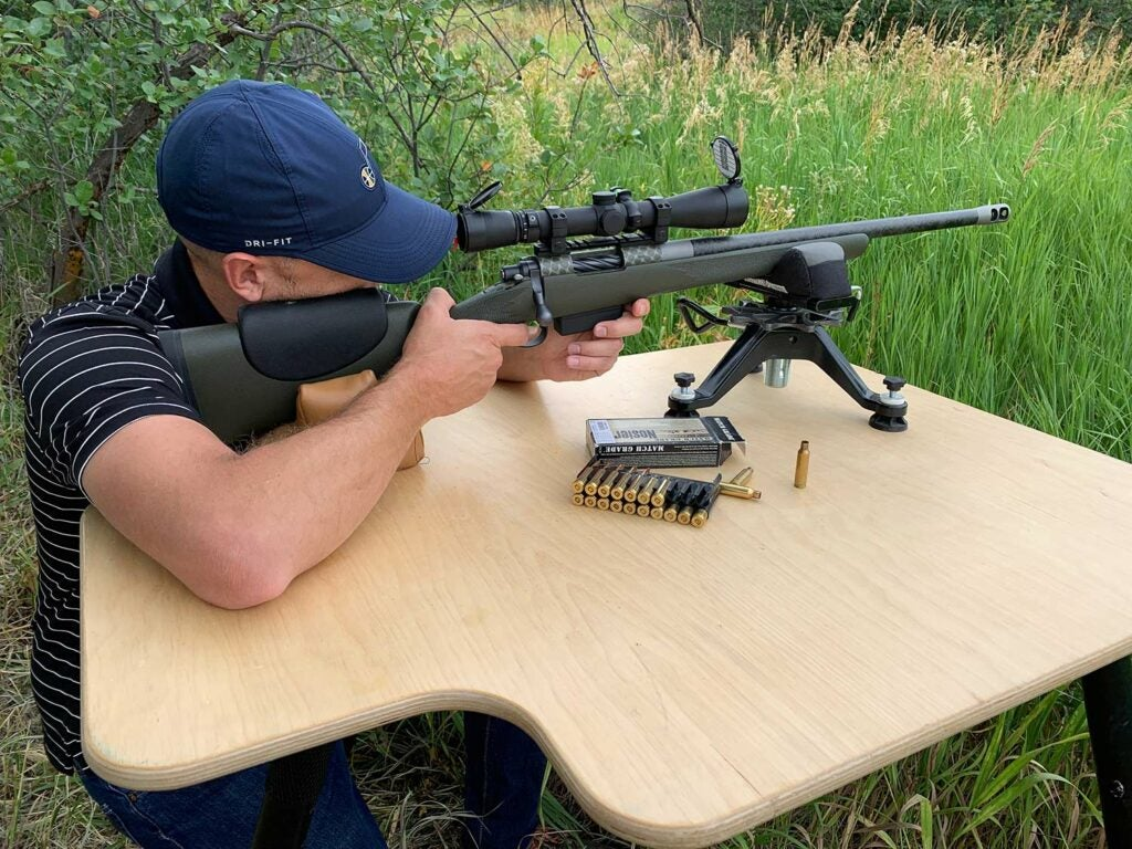 A man aiming a rifle propped on a table and shooting bipod.