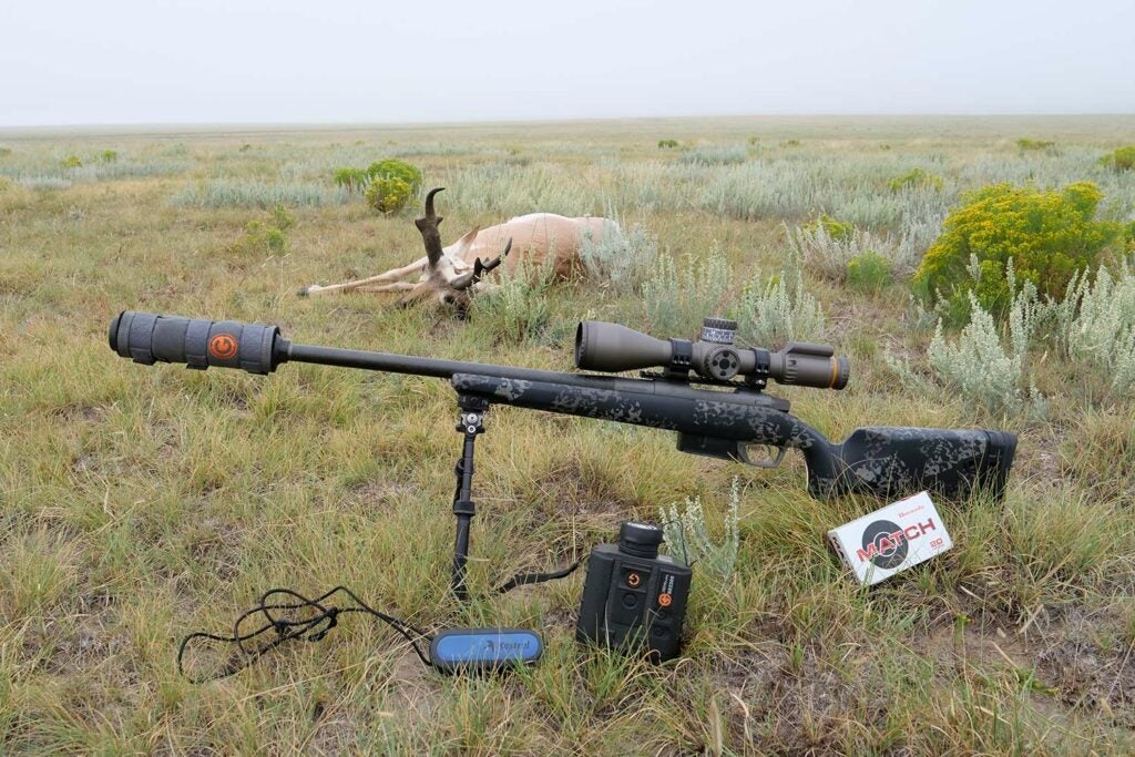 A rifle propped on shooting sticks in a field beside a deer.