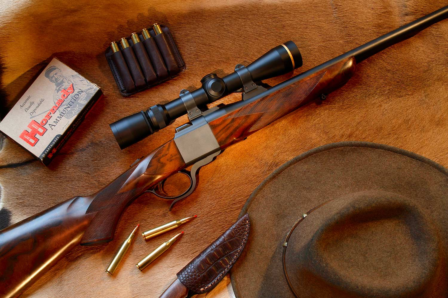 A hunting rifle and western hunting gear on a deer skin.