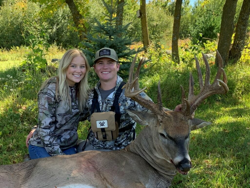 A smiling young man and woman in camo shirts sit behind a big whitetail buck.