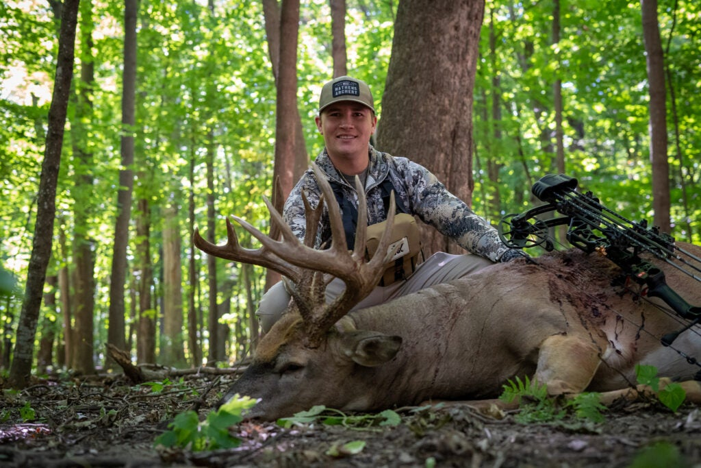 A grinning young bowhunter in camo and a ball cap sits behind a whitetail buck in green timber.