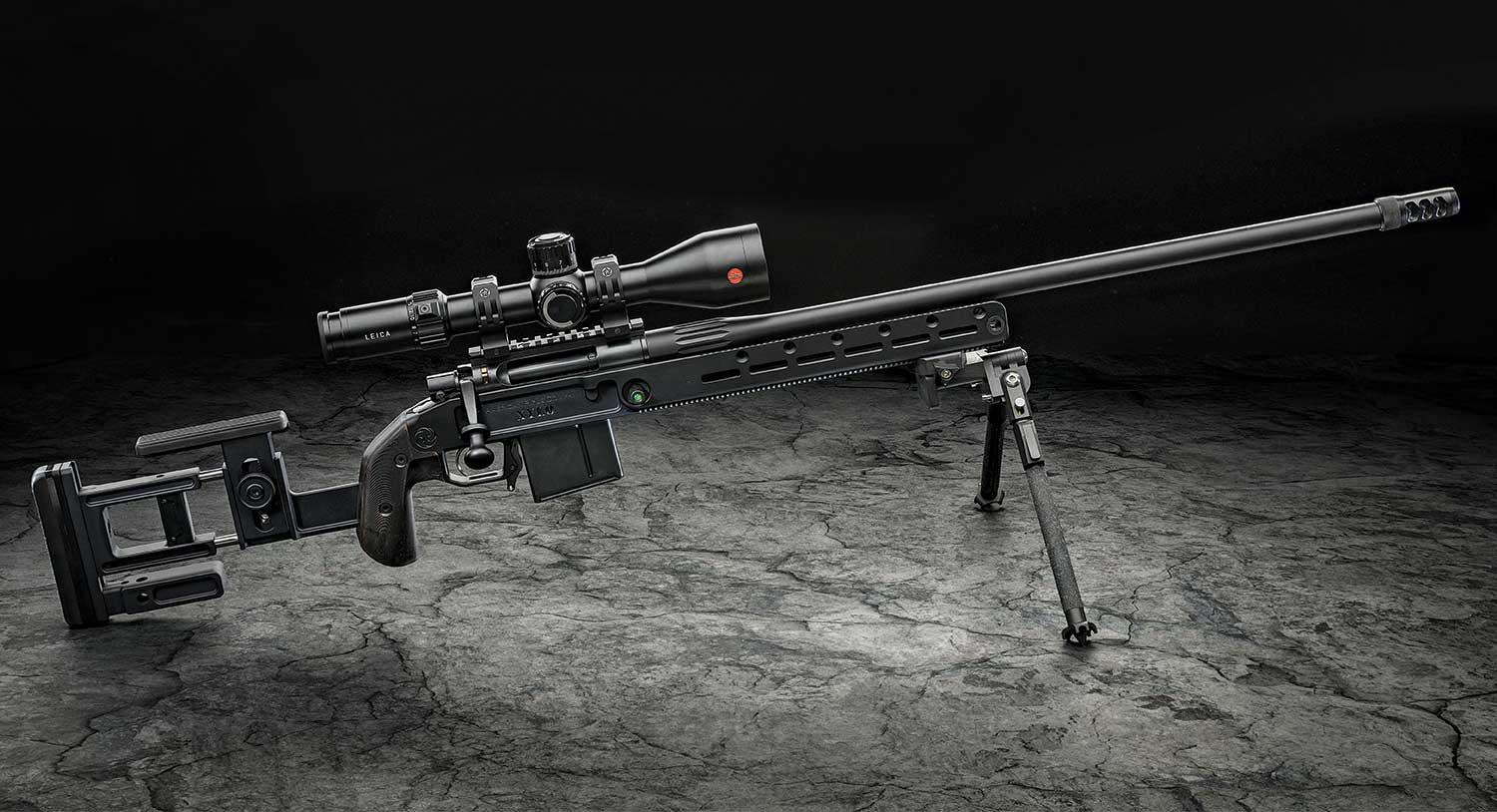 An American Rifle Company Nucleus Gen2 rifle on shooting sticks and a Leica Riflescope.
