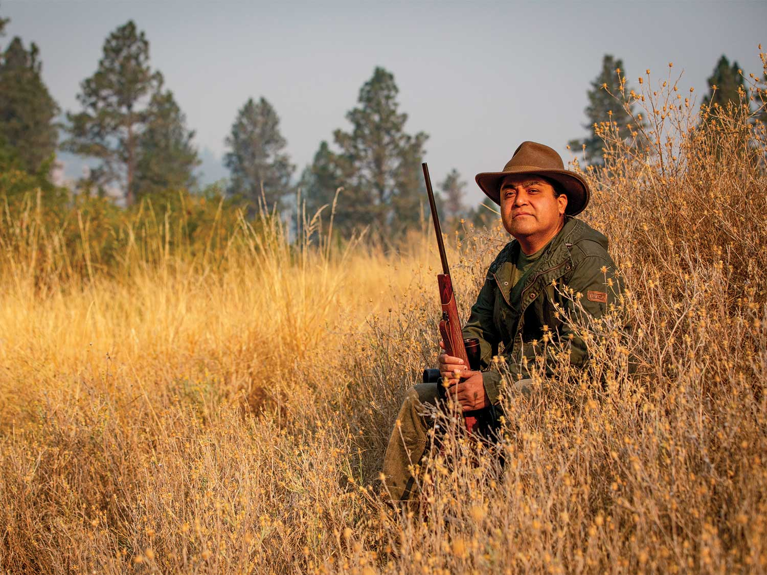 A native hunter, Josiah Pinkham, sits in a field of tall weeds and holds a rifle.