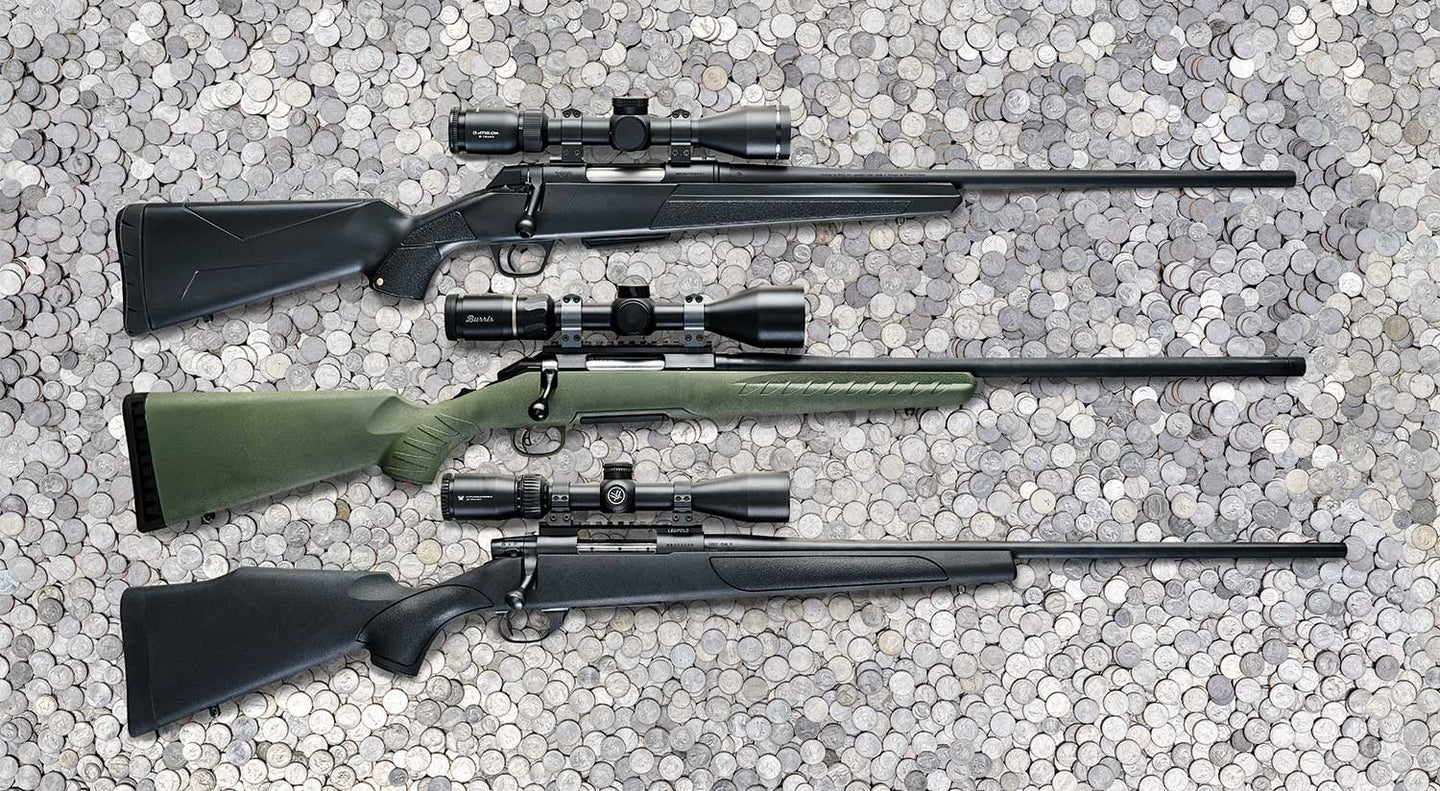 A lineup of three rifles with scopes on a bed of quarters.
