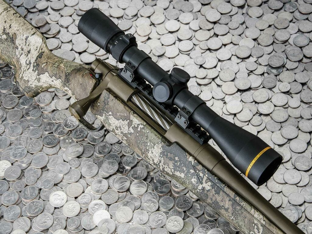A mossberg patriot rifle with a riflescope on a pile of quarters.
