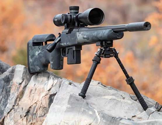 A rifle propped up on a rock using shooting sticks.