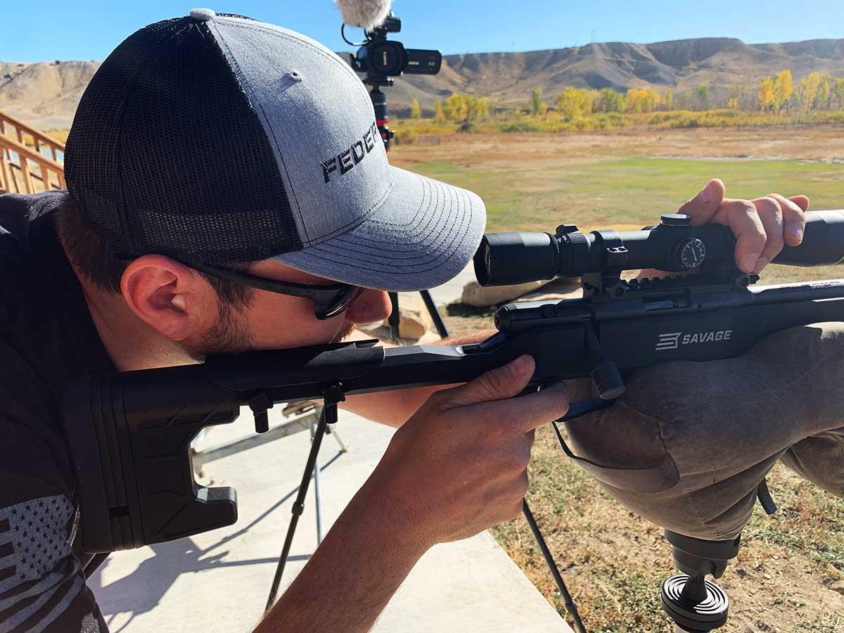 A man aims a rimfire rifle on a shooting range.