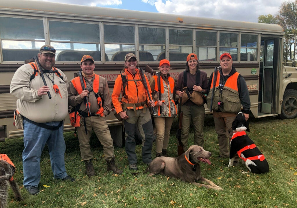 A group of hunters in orange in front of a school bus with several bird dogs.