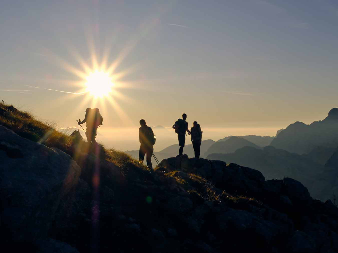 People at the top of a mountain at sunset