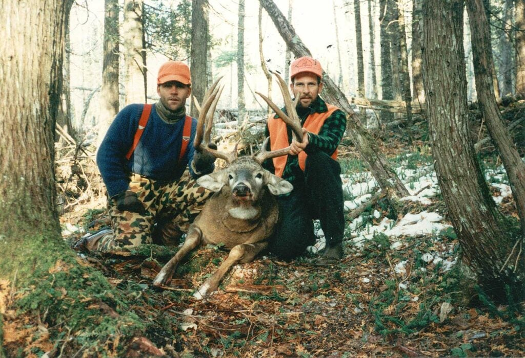 Two hunters kneel behind a large buck in the woods.