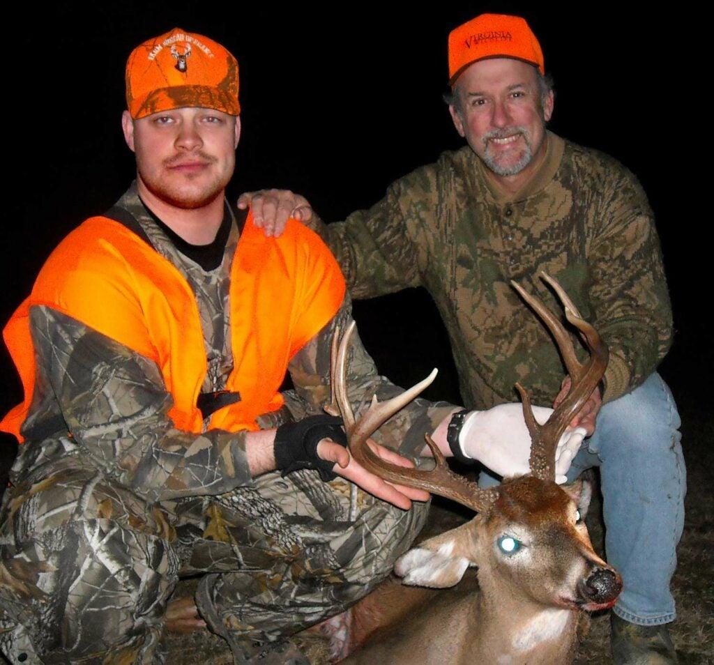 Two hunters kneeling behind a whitetail deer.