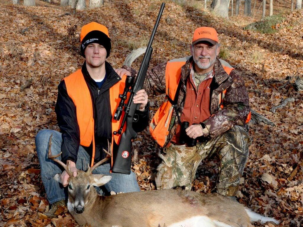 Two kneeling hunters behind a whitetail deer.